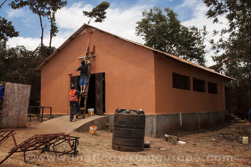 Un volontario e un tecnico dell'associazione tinteggiano la facciata di un laboratorio